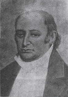A man with dark, receding hair wearing a high-collared white shirt and dark jacket