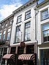 foto van Huis met witgeverfde lijstgevel en jongere winkelpui