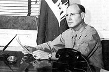 Man in shirt and tie sits at a desk. His shirt is neatly ironed. A telephone and writing pens are on the table. In the background is a US Army Corps of Engineers flag.