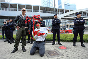"""Gui Minhai - Artist Kacey Wong protesting against the Causeway Bay booksellers disappearances. The sign in his hand says """"Hostage is well"""". 10 February 2016"""