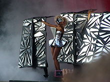 A blond woman standing on a stage, from her left. Her hair is in curls and she wears a shiny mask on her face. She wears a silvery tutu like dress with a triangular piece attached on her chest. The woman stretches her glove wearing arms to the front. Behind her, a number of vertical rectangular structures are visible on which geometric patterned glasses are attached. The rest of the stage is filled with mechanical fog.