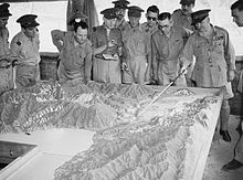 Men in military-style uniforms stand around a terrain model while one man points out terrain features with a pointer