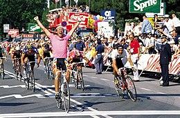 Photographie d'un coureur cycliste portant un maillot rose et levant les bras, devant d'autres coureurs cyclistes.