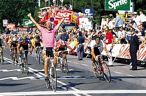 Fignon, wearing a pink jersey, throwing his arms up in celebration as he crosses the line in front of other riders.