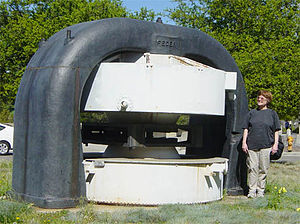 The magnet portion of a large cyclotron. The gray object is the upper pole piece, routing the magnetic field in two loops through a similar part below. The white canisters held conductive coils to generate the magnetic field. The D electrodes are contained in a vacuum chamber that was inserted in the central field gap.