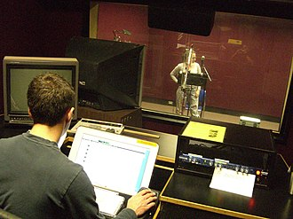 Lip sync - A voice actor (by the microphone) records a lip-synching track for an animated video production. Once her vocal part is recorded, audio engineers will then put her vocals into an animation production, to give the impression that an animated character is speaking.