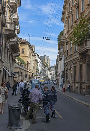 A narrow street slightly curving rightwards in the distance, above which are overhead wires and a blue sky. On either side are low multistory buildings painted in light colors with ornate architectural decoration. In the foreground are several men in police uniforms clustered in front of a motorcycle with a man in plain clothes, their backs to the camera. People are walking along both sides of the street.