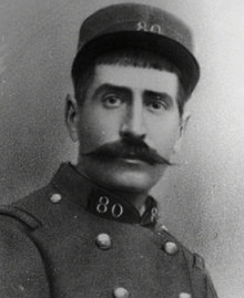 A black and white portrait photo of a man in French Army fatigues wearing a cap