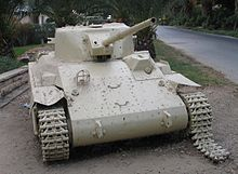 A beige-coloured Locust tank faces the camera, with its gun barrel pointing upwards slightly. Its right-hand track has been damaged and is falling off. The front section of the hull is missing two large loop-shaped handles that other examples possess. It is situated on grassland, with a road passing next to it.