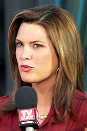 "An image of a woman with shoulder-length hair and a dark red outfit. She is speaking into a microphone with the words ""TV Guide""."