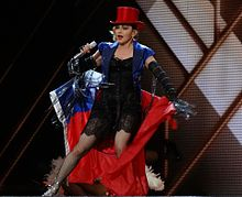 Madonna in a red hat and blue jacket with a red-and-blue flag wrapped around her performing onstage