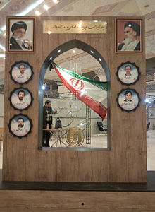 Indoor memorial, with photos and an Iranian flag