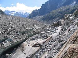 Phtographie. La surface de la langue glaciaire fissurée, est recouverte de blocs rocheux de tailles diverses, qui sont tombés des parois