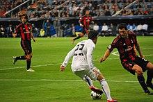 acb885337 Özil taking on Daniele Bonera of Milan during the 2010–11 UEFA Champions  League