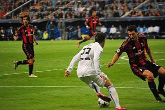 Mesut Özil - Özil taking on Daniele Bonera of Milan during the 2010–11 UEFA Champions League