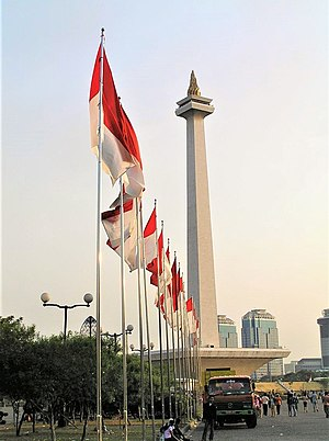 Flag of Indonesia - The National Monument with a row of Indonesian flags