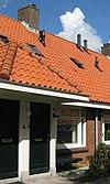 foto van Blok met 9 woningen, gecombineerde toegangen van twee woningen onder een ingestoken schilddak, zijkant met houten topgevel, onderdeel van complex bejaardenwoningen in Tuindorp Nieuwendam