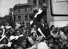 Men wearing different clothes are marching while in their center there is a man standing on a car, while holding his hand up with a towel. There are men in military uniform, some in Jellabiyas and others in jackets.