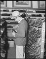 Oakland, California. Youth on Relief. This young agricultural migrant is buying a second hand hat and shoes in the... - NARA - 532144.tif