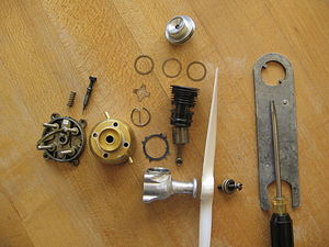 Two-stroke engine - A Cox Babe Bee 0.049 cubic inch (0.8 cubic cm) reed valve engine, disassembled, uses glow plug ignition. The mass is 64 grams.
