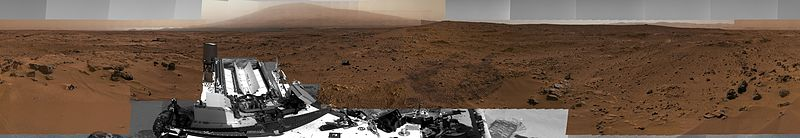 "جوال كيريوزيتيقالب:'s view of the ""Rocknest"" area - South is center/North at both ends; ""Mount Sharp"" at SE horizon (somewhat left-of-center); ""Glenelg"" at East (left-of-center); rover tracks at West (right-of-center) (November 16, 2012; توازن لوني) (raw color) (interactives)."