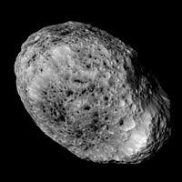 Un cuerpo de forma irregular y lleno de cráteres, marcado con picaduras oscuras y crestas en su superficie helada de color tostado.