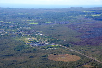 Puʻu ʻŌʻō - March 2015. Looking south toward the town of Pāhoa, and southwest toward the lava flow from Pu'u 'O'o – outlined by burned vegetation.