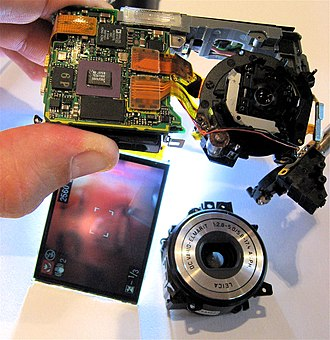 Digital camera - Digital camera, partly disassembled. The lens assembly (bottom right) is partially removed, but the sensor (top right) still captures an image, as seen on the LCD screen (bottom left).