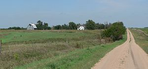 Dirt road running through gently rolling grassland; house and barn on near horizon