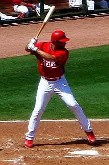 A right-handed man in a red batting practice baseball jersey and white baseball pants with red pinstripes stands in a batter's box by home plate.