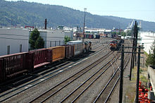 Two trains head in opposite directions along tracks in a switching yard surrounded by warehouses.