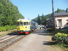 Blue-and-yellow railbus at a rural station
