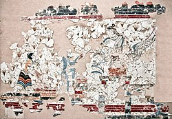 Η Πότνια Θηρών καθήμενη σε περίοπτη θέση, δέχεται προσφορές κρόκων που έχουν συλλεχθεί από μια γυναίκα και έναν πίθικο - τοιχογραφία Ακρωτήρι Θήρας