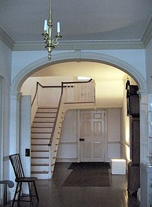 A photograph of the main stairway and hallway of a house, painted white.