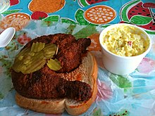 Hot chicken sitting on a piece of bread alongside other toppings and condiments