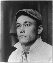 An old picture of a man wearing a baseball cap looking to the photographer's left.