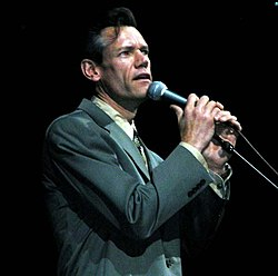 A dark-haired man in a grey sports coat singing into a microphone