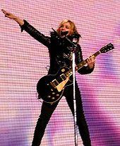 O femeie îmbrăcată în negru ținând o chitară și stând în spatele unui suport de microfon cu un braț întins direct în aer.  În fundal este un ecran cu nuanțe de roz și violet.
