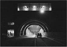 Black-and-white photo of highway tunnel at night