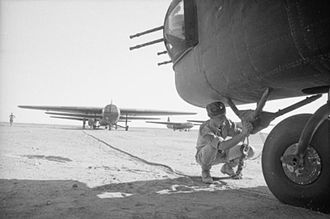 Military glider - An RAF airman attaches the tow rope of an Airspeed Horsa glider to the tow hook of a Handley Page Halifax glider tug, in preparation for Operation Fustian, Tunisia (July 1943)