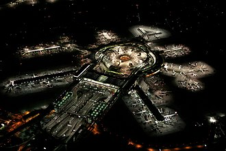 International airport - San Francisco International Airport at night, with departure gates radiating out from the terminal building, aerobridges, apron, and parked planes