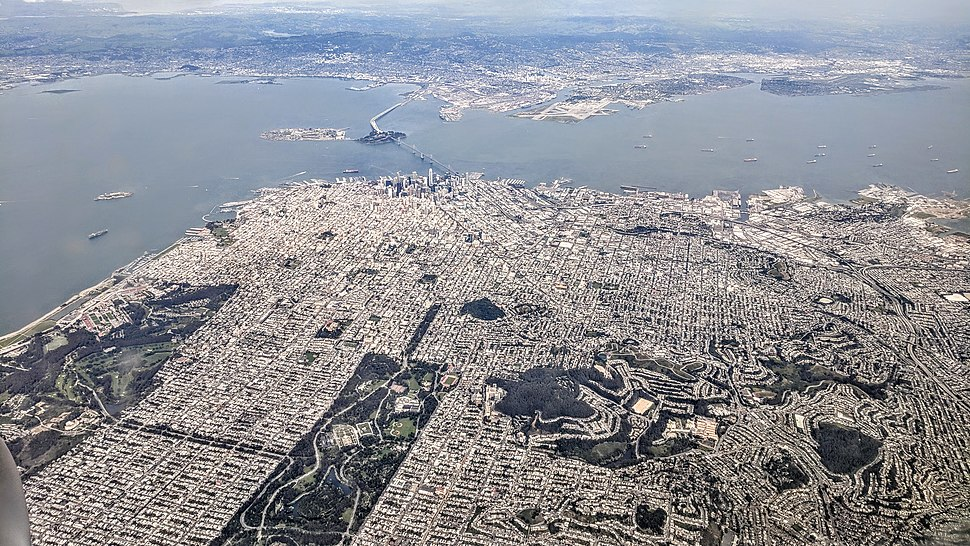 Aerial view from the west in April 2018. San Francisco is seen in the foreground, with Oakland in the background.