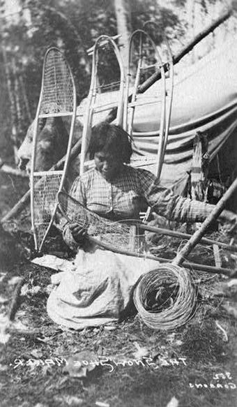 Black and white photo of a woman kneeling on the ground making a snowshoe. She is wearing a plaid shirt and white dress locking down at the snowshoe. Around her is four frames of snowshoe to be made leaning on a tippy,