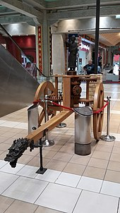 A wooden two-wheeled cart supporting a series of wooden peg gears and a metal statue pointing with one outstretched hand.