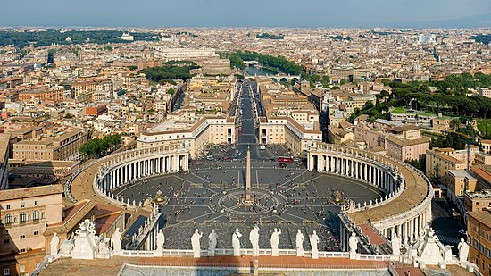 At the front of the view are the backs of thirteen large statues that stand in along the edge of the facade. Beyond them can be seen the piazza which is in three parts. The nearest appears square, while the second widens into an oval surrounded on each side by the huge grey columns on the colonnade, and with the obelisk at its centre. Beyond that is a further square surrounded by pale pink buildings. A wide street leads from the square, at the end of which can be seen the river, a bridge and castle.