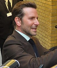 Bradley Cooper is looking to his left.