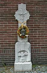 Wegkruis van naamse steen met corpus in reliëf
