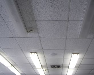 Dropped ceiling - Dropped ceiling, after installation. Light fixtures, a speaker grill, smoke detectors, and an air grill are all visible.
