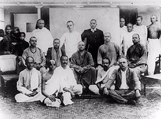 Vivekanandar Illam - Swami Vivekananda (on the chair, third from left) and Biligiri Iyengar (on the floor, second from left) at the Ice House in 1897