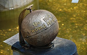 The World Peace monument in a pond next to a s...